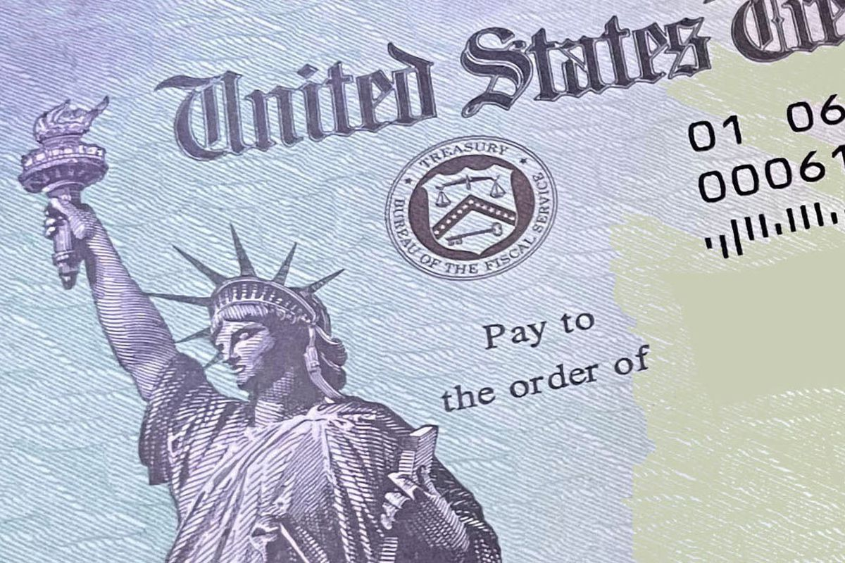 A blue and green check features a black and white rendering of the Statue of Liberty, the seal of the US Treasury, and a field for the recipient's name.