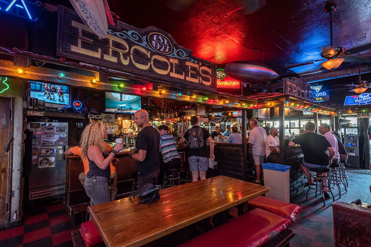 A dive bar lit up in neon with an old wooden sign above the bar.