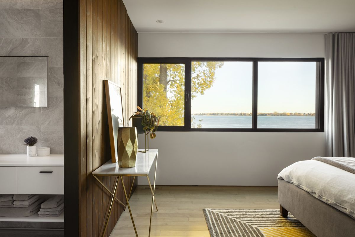 Bedroom has large windows with river views.