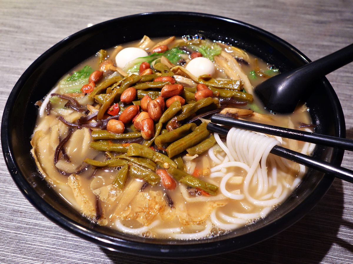 A noodle dish with bamboo shoots, quail eggs, lettuce, sour beans, and fried peanuts.