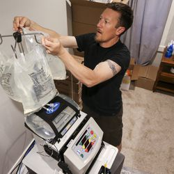 Zach Thomas hangs bags of Dialysate on his at-home dialysis machine before he starts his treatment at his home in Kamas on Sunday, Sept. 8, 2019. Because of all the steps that need to be take before dialysis, Thomas didn't start treatment until April of 2019, nearly a year and a half after his diagnosis of kidney failure.