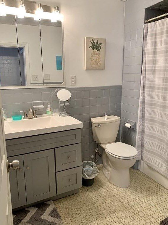 A bathroom with a small vanity next to a toilet next to a shower with the curtain pulled across.