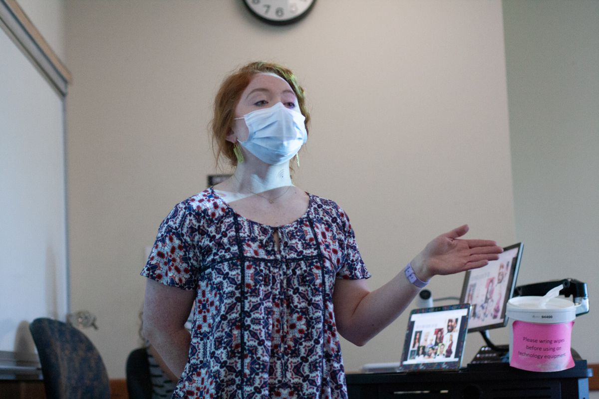 A young woman wearing a mask and patterned shirt speaks at the front of a classroom, with computer monitors sitting on a desk behind her.
