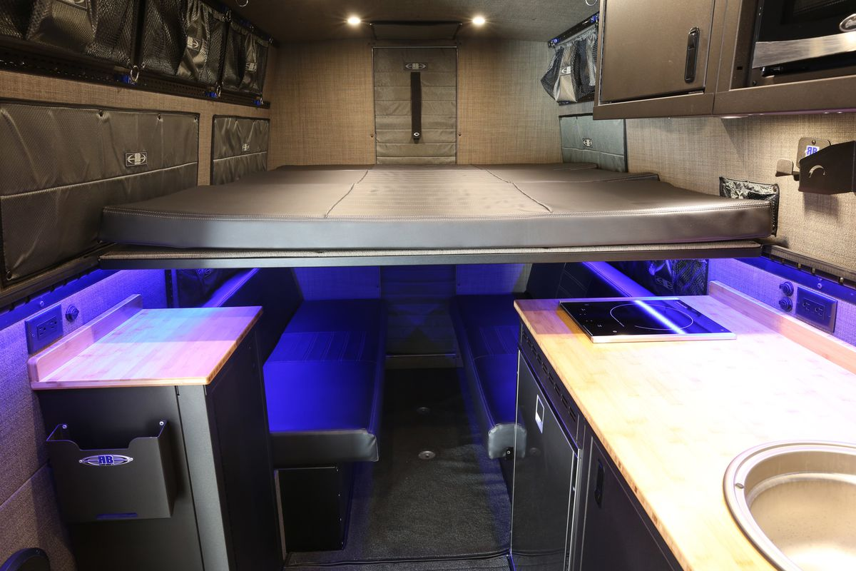 The interior of a camper van. There is a kitchenette with a sink and stove, a bed, and various cabinets.