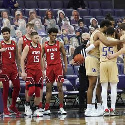 Washington players huddle at right as Utah players look on during the second half of an NCAA college basketball game, Sunday, Jan. 24, 2021, in Seattle. Washington won 83-79.