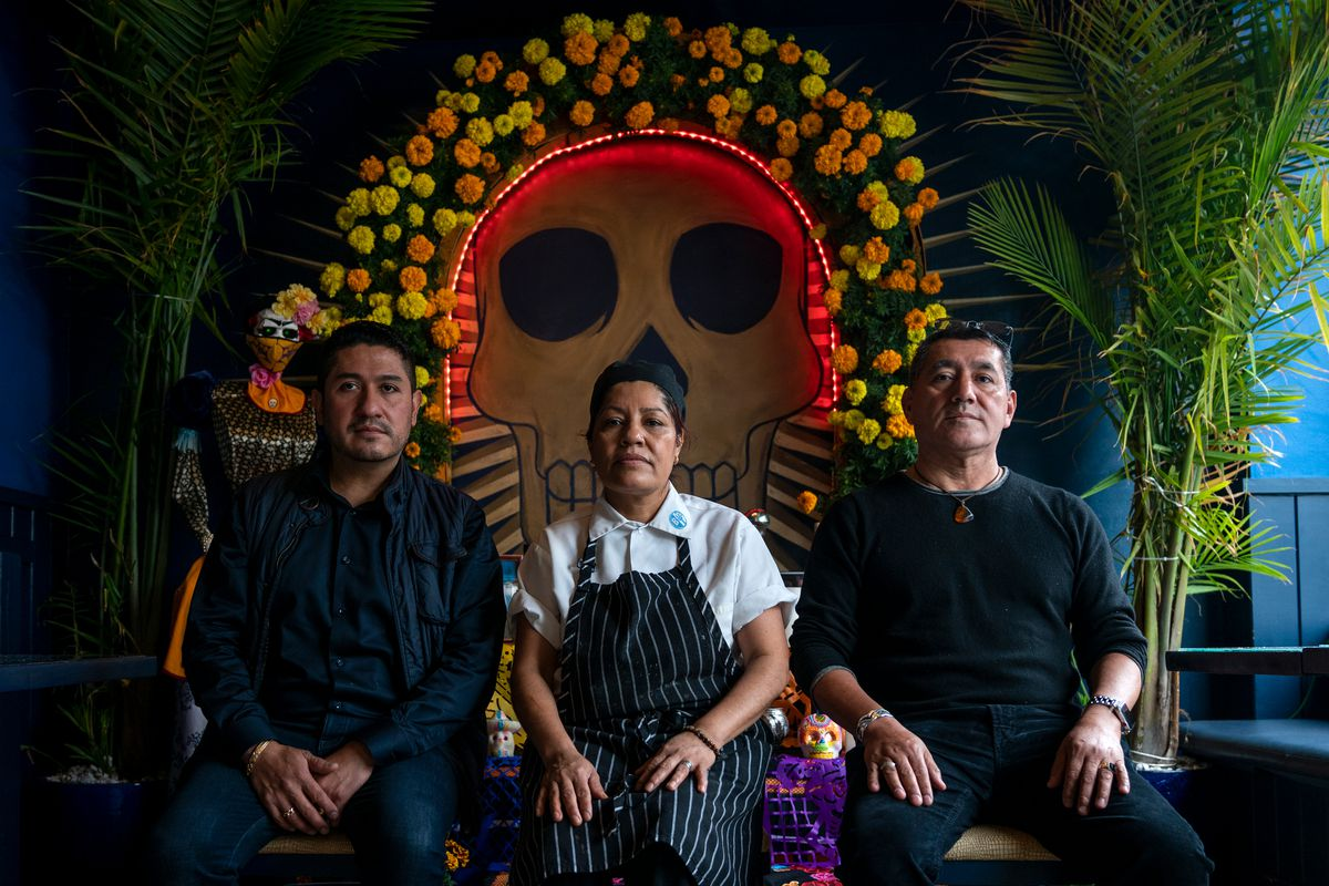 Casa Azul owners Alfonso Emilio Sanchez, left, Rifuna Lopez and Roberto Lopez created an alter at their Brooklyn restaurant as a safe way for people to honor their loved ones during the coronavirus outbreak, Oct. 27, 2020.
