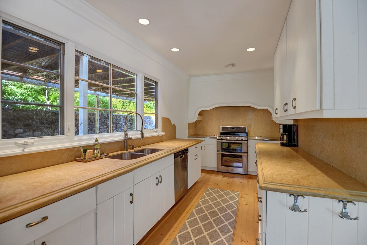 A long, narrow kitchen features stone counters with white cabinets and a stove at one end.
