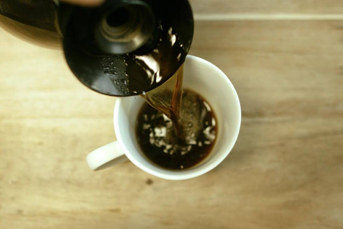 A photo of coffee being poured into a cup