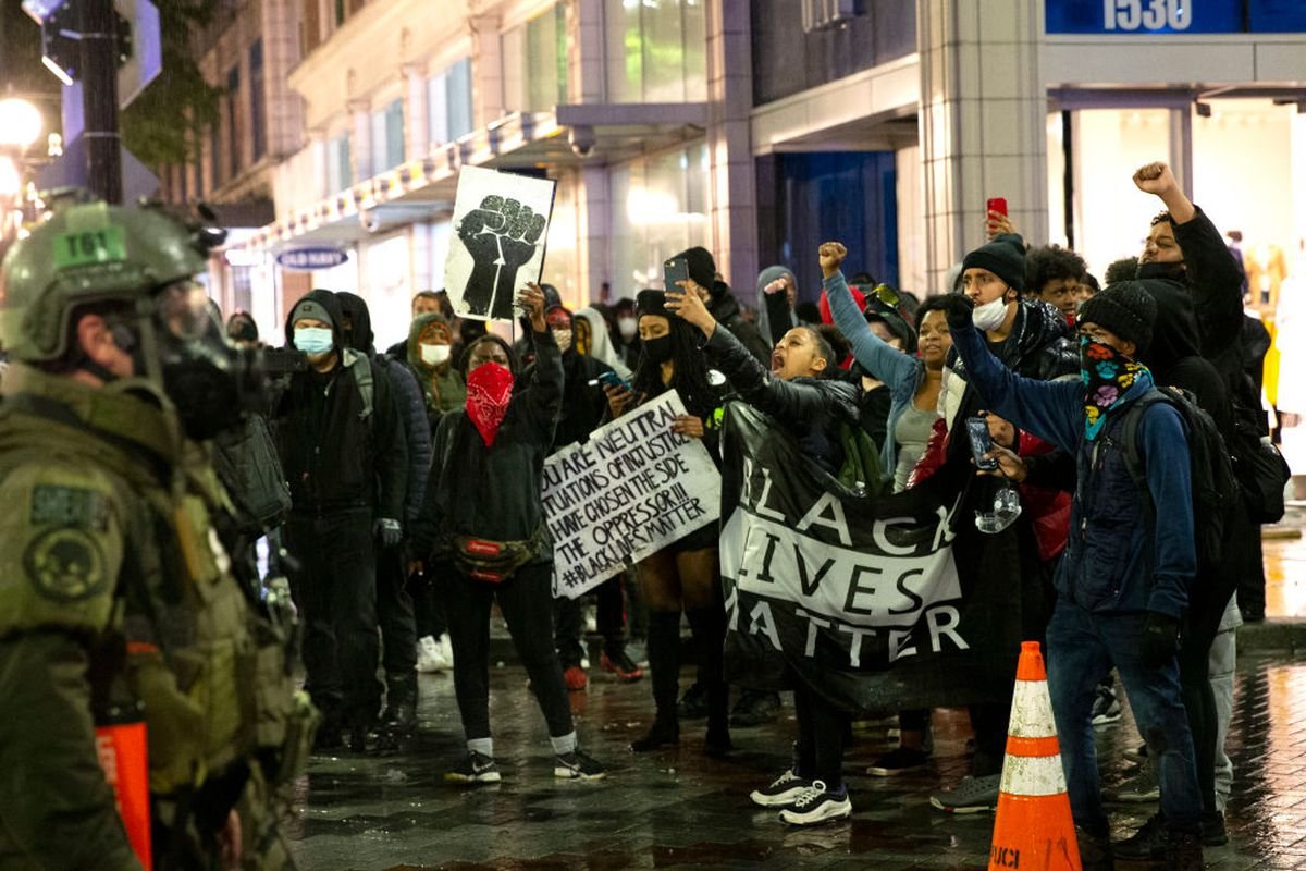 A group of protesters displaying Black Lives Matter signs face heavily-outfitted police on the streets of Seattle.