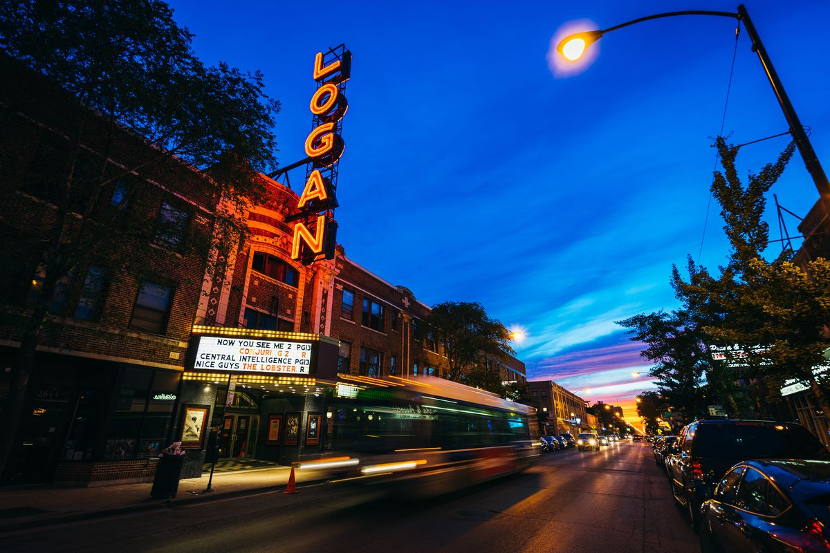 A red neon sign that reads 'Logan' for the Logan Theater glows at night in Chicago.