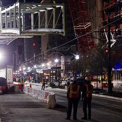 Construction workers watch as a skybridge is hoisted above Main Street and lowered in to place connecting the City Creek Center development in downtown Salt Lake City Sunday.