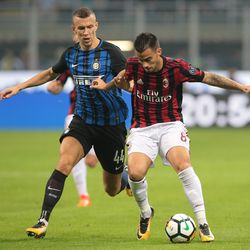 Fernandez Suso of AC Milan (R) competes for the ball with Ivan Perisic of FC Internazionale Milano during the Serie A match between FC Internazionale and AC Milan at Stadio Giuseppe Meazza on October 15, 2017 in Milan, Italy.