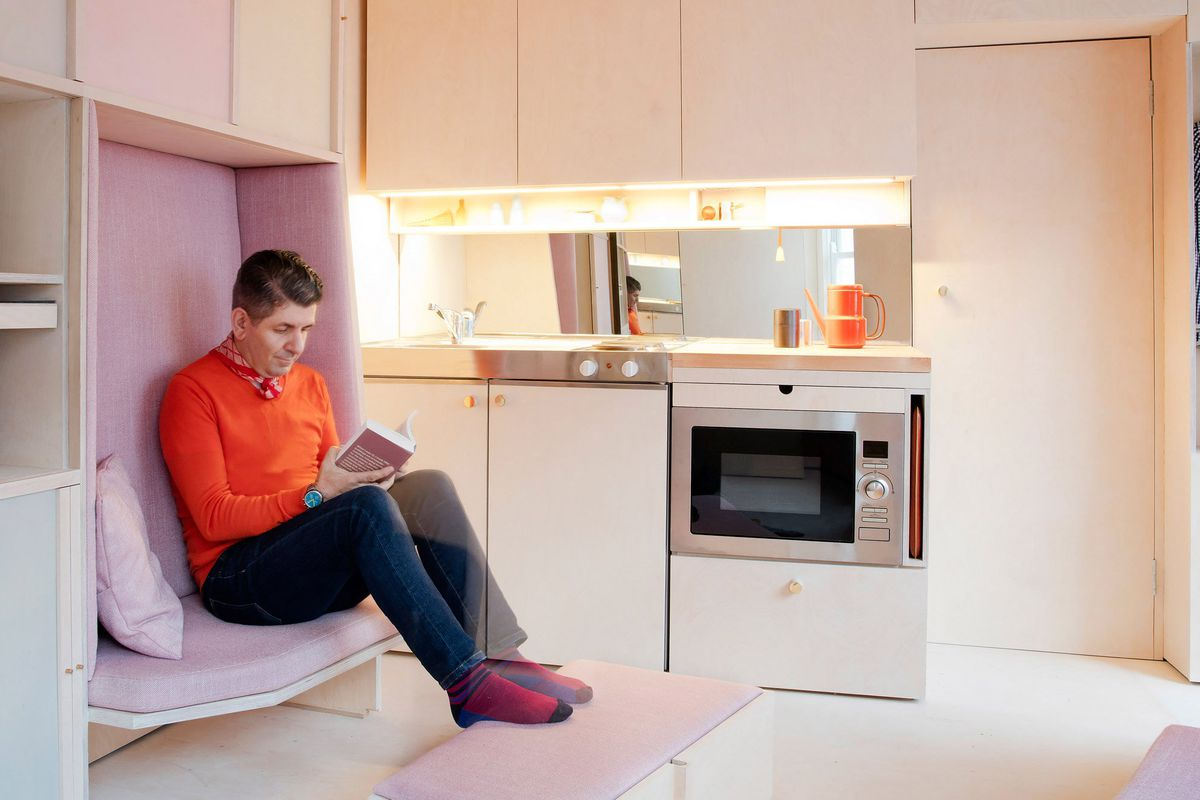 Interior shot of plywood-clad tiny home showing a small kitchen and a nook sofa built into wall of shelves and upholstered with light pink cushions.