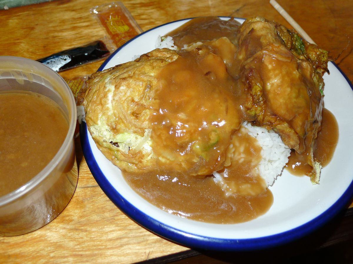 Egg foo young with plenty of brown gravy and white rice.