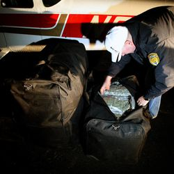 Uintah Basin Narcotics Strike Force commander Mike Gledhill opens one of four duffel bags filled with marijuana that authorities found inside a Cessna 182 Skylane after it landed Tuesday, Nov. 12, 2013, at the Vernal Regional Airport. The drugs were discovered when investigators called in a police K-9 to search the plane after receiving a tip from the U.S. Department of Homeland Security. Police arrested the pilot.