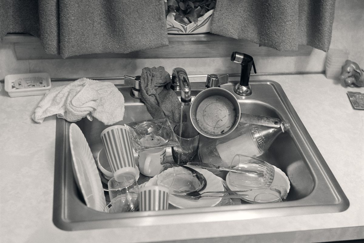 A black and white photo of a kitchen sink full of dirty dishes.