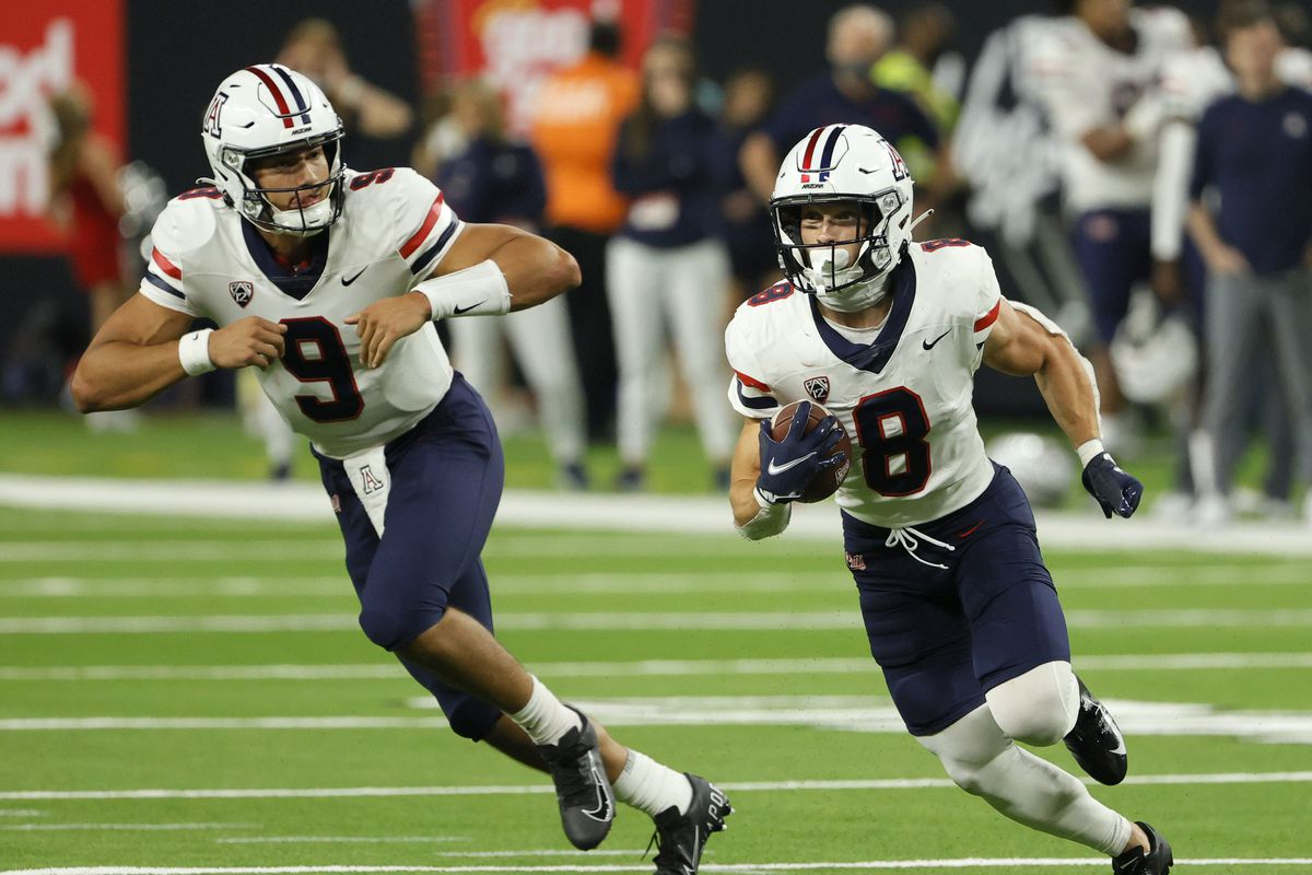 Running back Drake Anderson of the Arizona Wildcats runs in front of quarterback Gunner Cruz against the Brigham Young Cougars during the Good Sam Vegas Kickoff Classic at Allegiant Stadium on September 4, 2021 in Las Vegas, Nevada.