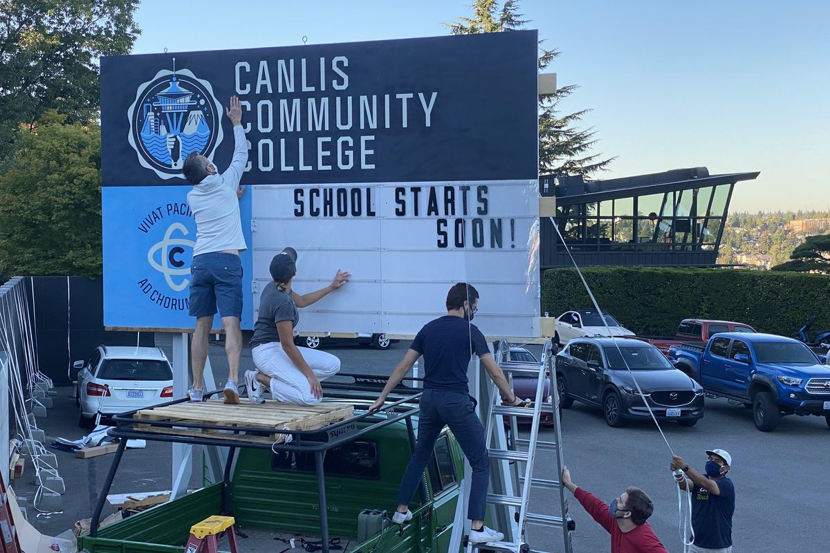 """Three men hang up lettering on a sign outside Canlis that says """"Canlis Community College."""""""
