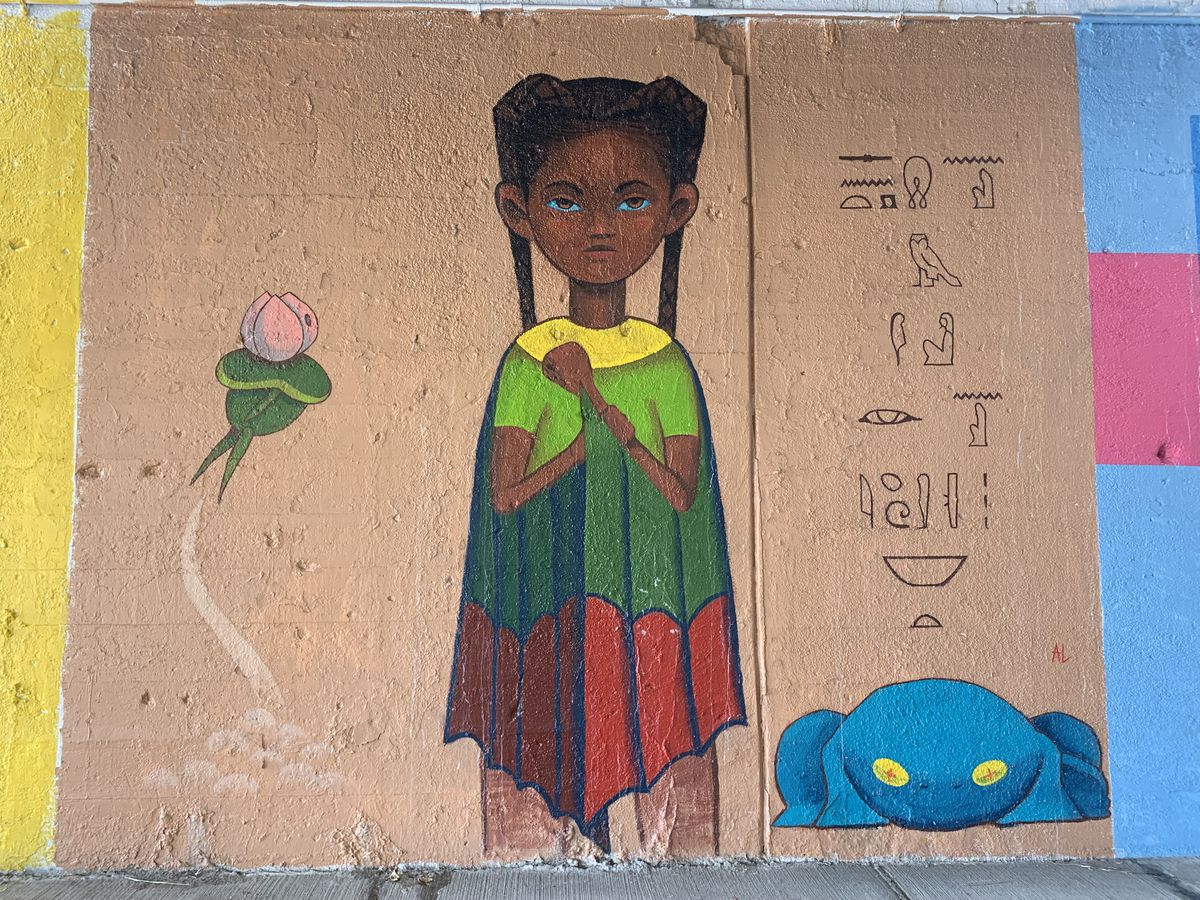 """This mural, by a Southeast Side artist who goes by Asteroid Lloyd, features a girl he says is """"all for justice. She's from Chicago. She's a character on the quest for knowledge and finding herself."""" Hieroglyphics also are part of this painting, as are a lotus flower and a frog."""