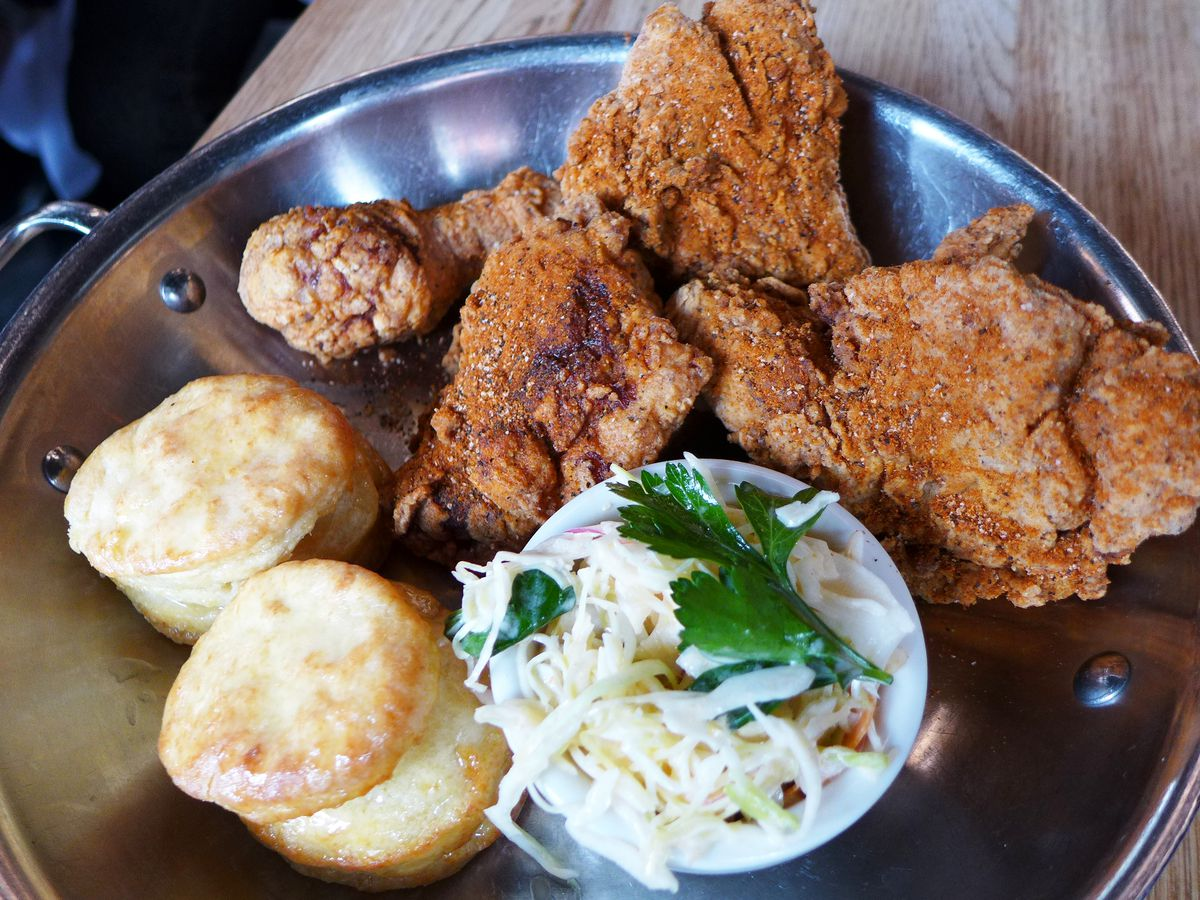Fried chicken, slaw, and small biscuits served in a metal bowl