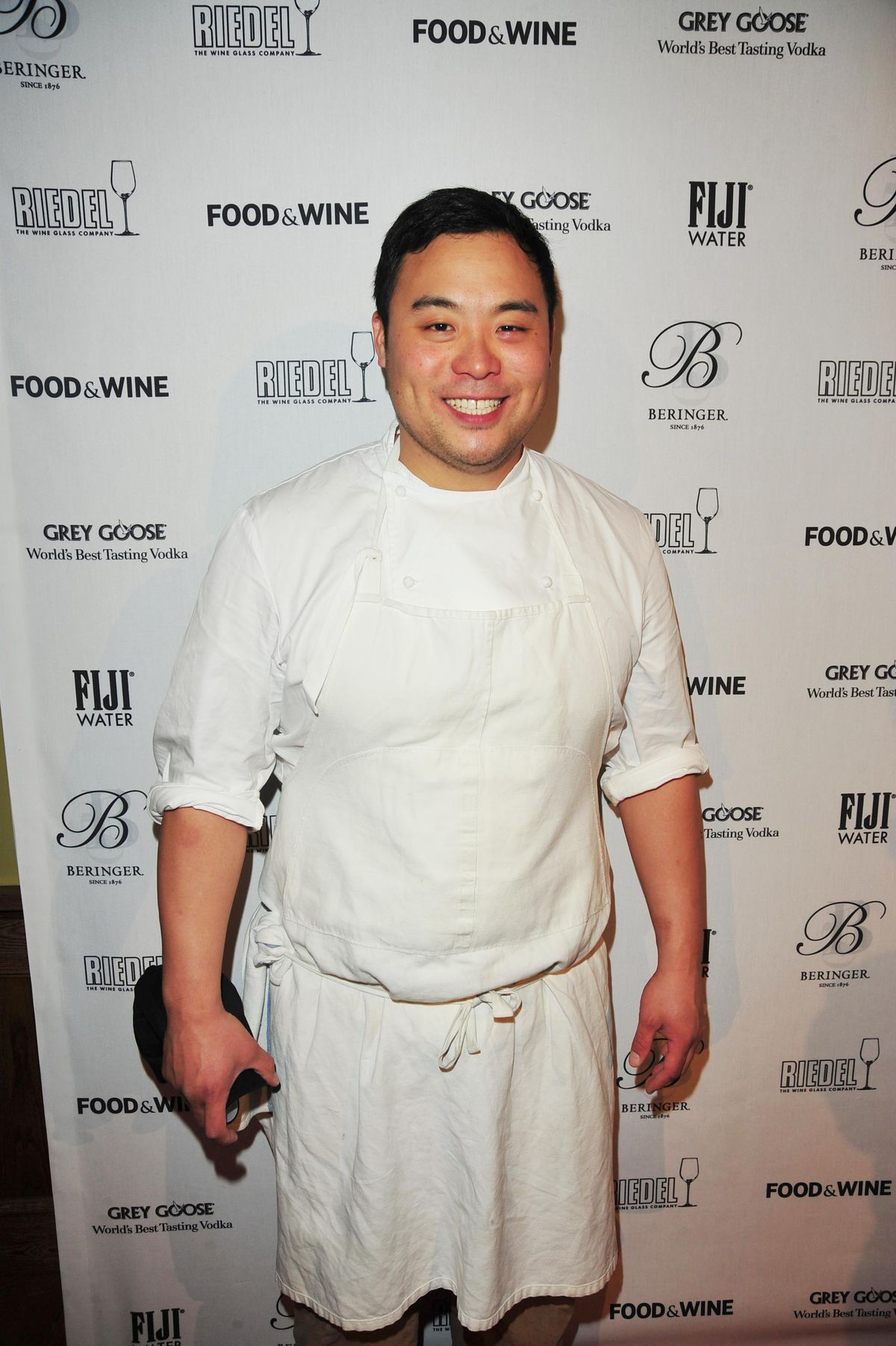 A young David Chang wears a white apron and chef's white in front.