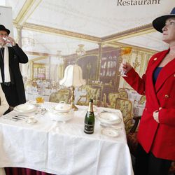 Carmel Bradbam and Andreas Stovic , both at left, from Adelaide, Australia drink champagne as they sit in a mock up of a first class dinning table of the Titanic in the check in area for the MS Balmoral's Titanic memorial cruise in Southampton, England, Sunday, April  8, 2012. Nearly 100 years after the Titanic went down, a cruise with the same number of passengers aboard is setting sail to retrace the ship's voyage, including a visit to the location where it sank. The Titanic Memorial Cruise is set to depart Sunday from Southampton, where the Titanic left on its maiden voyage. The 12-night cruise will commemorate the 100th anniversary of the sinking of the White Star liner. With 1,309 passengers aboard, the MS Balmoral will follow the same route as the Titanic. Organizers are trying to recreate the onboard experience  minus the disaster from the food to a band playing music from that era. Organizers said people from 28 countries have booked passage, including relatives of some of the more than 1,500 people who died when the Titanic collided with an iceberg and sank on April 15, 1912. Woman at right declined to be named.