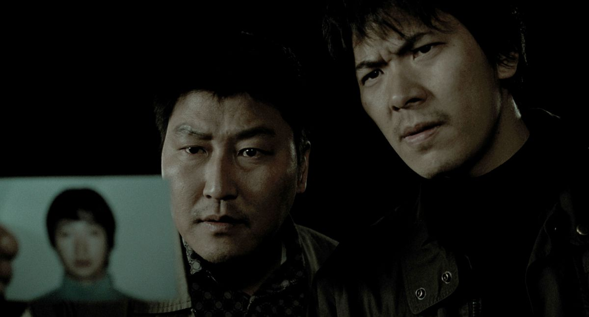 Detective Park (Song Kang-ho) and Seo (Kim Sang-kyung) holds the photo of murder suspect Park Hyeon-gyu (Park Hae-il ) in Memories of Murder
