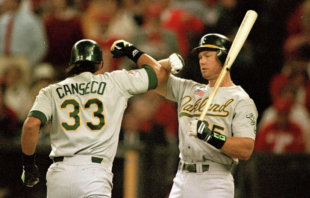 """Cincinnati, OH Ocotber 17, 1990: Jose Canseco, left, and Oakland Athletics teammate Mark McGwire, exchange their """"Bash Brothers"""" salute after Canseco homered during game two of the 1990 World Series against the Cincinnati Reds at Riverpoint Stadium. (Jose"""