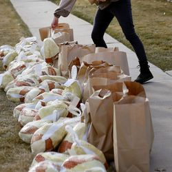 Mia Palmer organizes turkeys and bags of food at a Crossroads Urban Center food distribution event at Rowland Hall in Salt Lake City on Wednesday, Dec. 23, 2020. This year's Christmas food distribution marks the 23rd year of collaboration with Rowland Hall. Crossroads has been providing social services to individuals and families in need in Salt Lake City and the surrounding areas for over 50 years. Funding and support for the Christmas food distribution came from the staff, students and families of Rowland Hall, the Utah Food Bank, the Eccles Broadcast Center at the University of Utah, the B.W. Bastian Foundation, Rocky Mountain Power, and dozens of other individuals and local religious congregations.