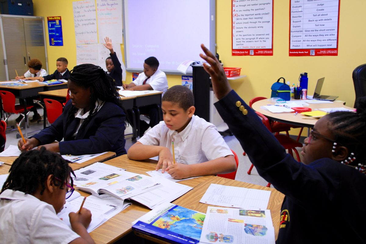 Students raise their hands during a lesson at STAR Academy.