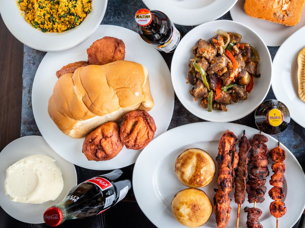 an overview spread of a table filled with African food including jollof rice and condiments