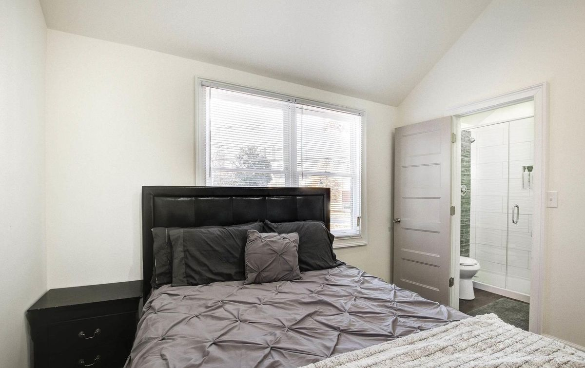 Bedroom with bed and nightstand with view into the bathroom in the back.