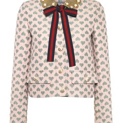 This heart motif skirt suit in gauffré is finished with a leather pearl collar and contrasting necktie.