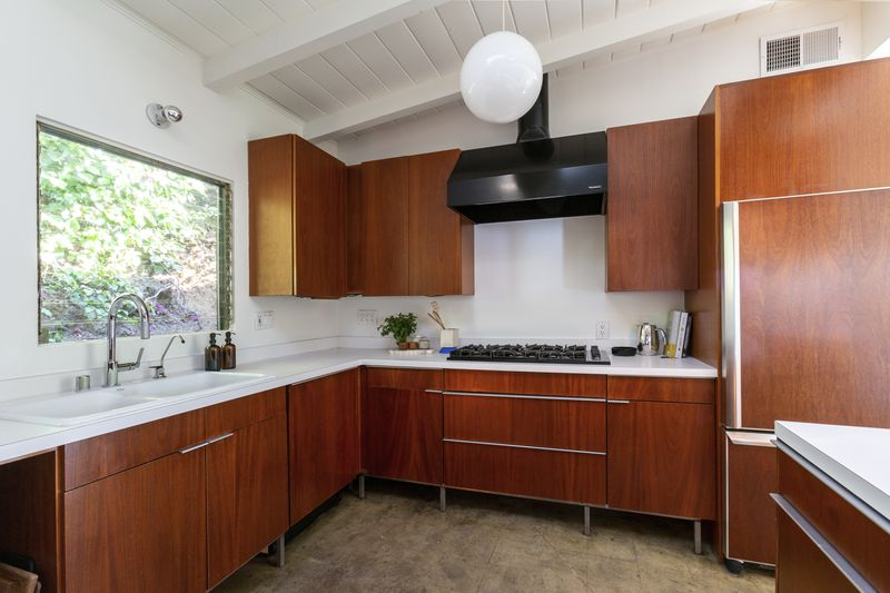 Kitchen with wood cabinets and black range hood.