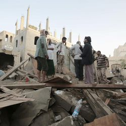 People stand on the rubble of houses destroyed by Saudi-led airstrikes in Sanaa, Yemen, Friday, Jun. 9, 2017. Three siblings and their grandmother were killed early Friday after Saudi-led coalition forces dropped munitions on three houses in the Yemeni capital, the children's father said.