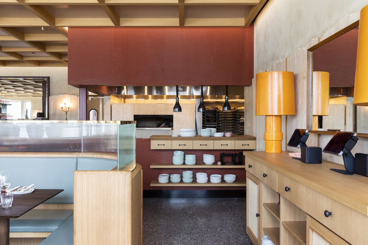 Rosie Cannonball's kitchen, with red tile and light blue stoneware dishes stacked on wood shelves