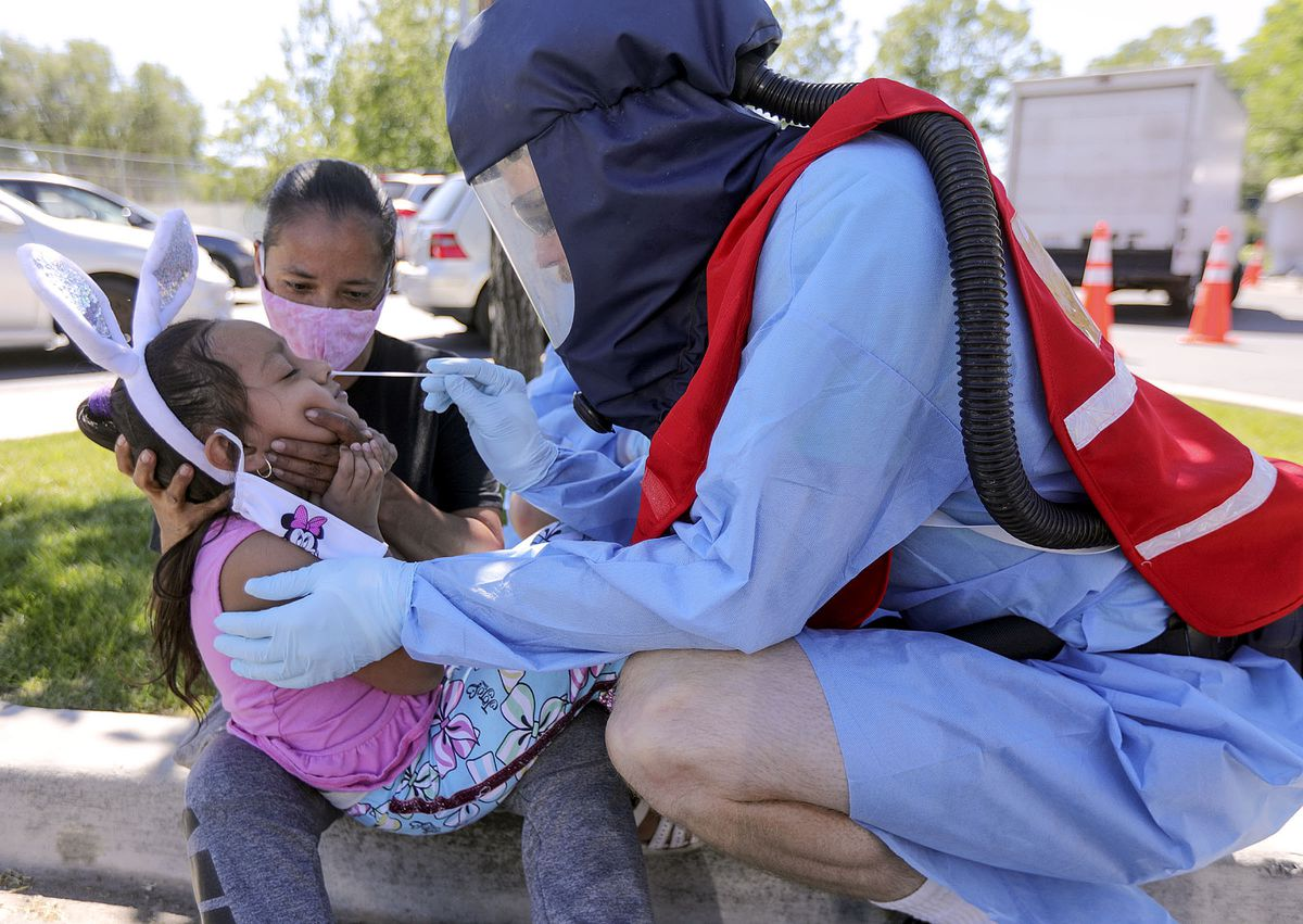 Medical Reserves Corps Mobile Testing Team administrator Aaron Dayne Smith tests Yareli Bermudez for COVID-19 as she sits on the lap of her mother, Elsa Burmudez, outside of Glendale Middle School in Salt Lake City on Monday, June 22, 2020.