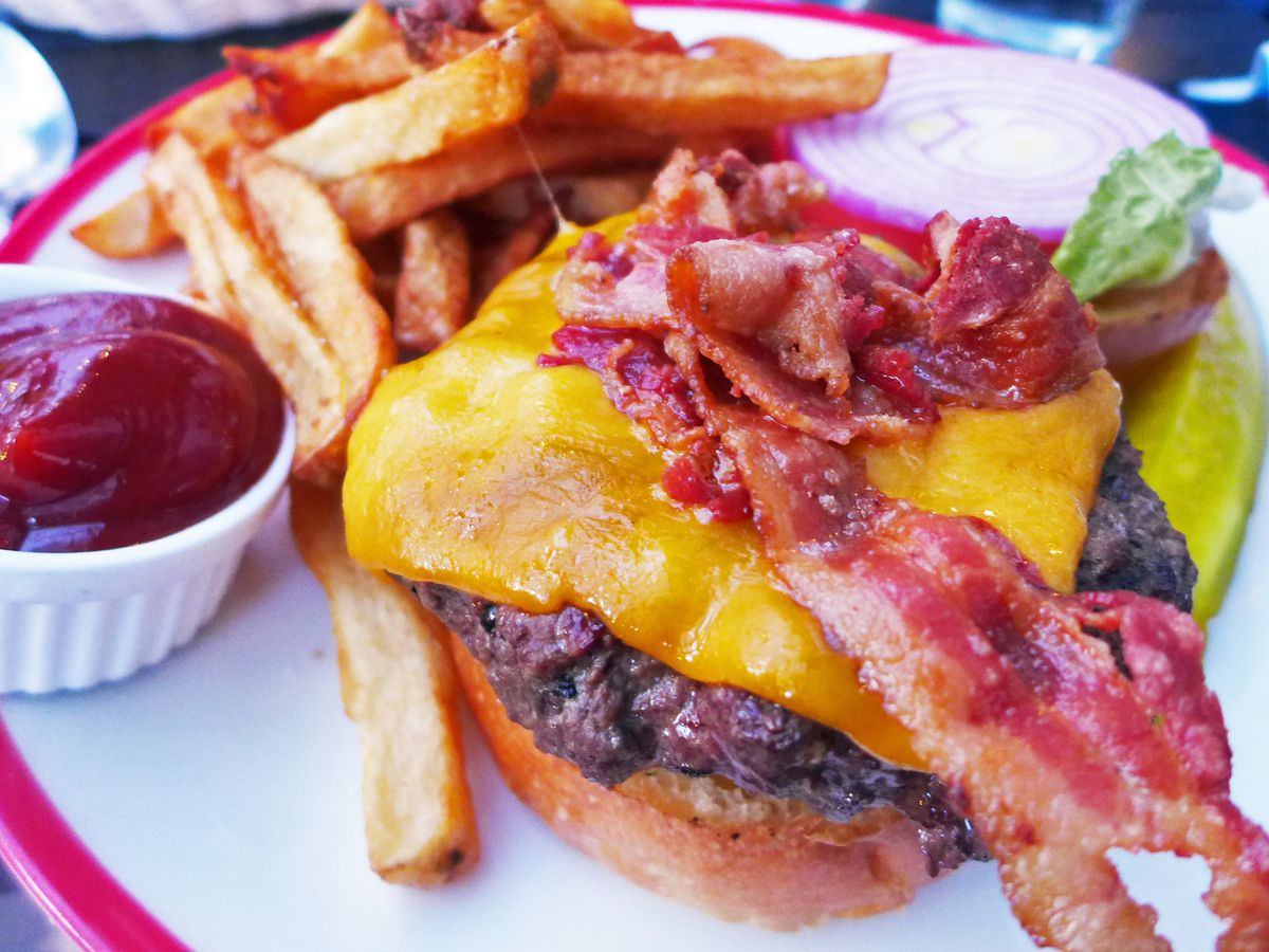 In the foreground a giant burger with top bun not affixed, showing yellow cheese and piled up bacon.