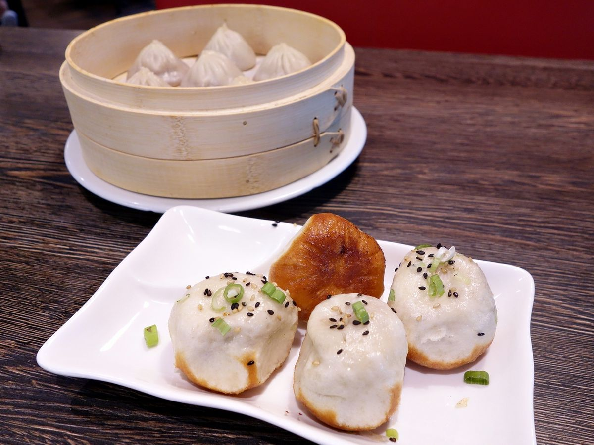 In the foreground, a plate of crispy dumplings; in the background, a wooden vessel filled with steamed dumplings.