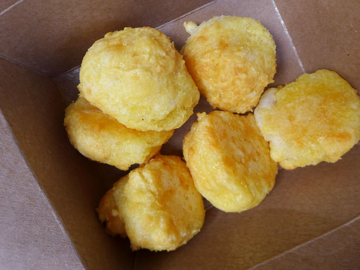 Six yellowish round cheese balls in a waxed cardboard box.