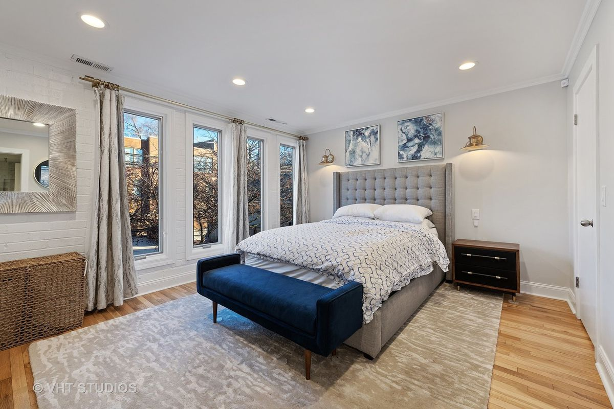 A bedroom with two gold sconces on either side of the bed. There is a large window with curtains and a blue bench at the end of the bed.