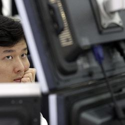 A currency trader looks at monitors at the foreign exchange dealing room of Korea Exchange Bank headquarters in Seoul, South Korea, Monday, April 9, 2012. Asian stock markets declined Monday after U.S. hiring slowed in March, raising doubts about the durability of the recovery in the world's No. 1 economy.  The Korea Composite Stock Price Index fell 1.57 percent, or 31.95, to close at 1,997.08.