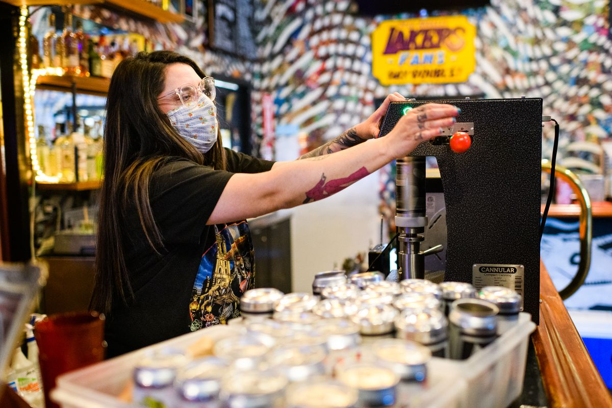 A woman operates a canning machine wearing glasses and a mask.