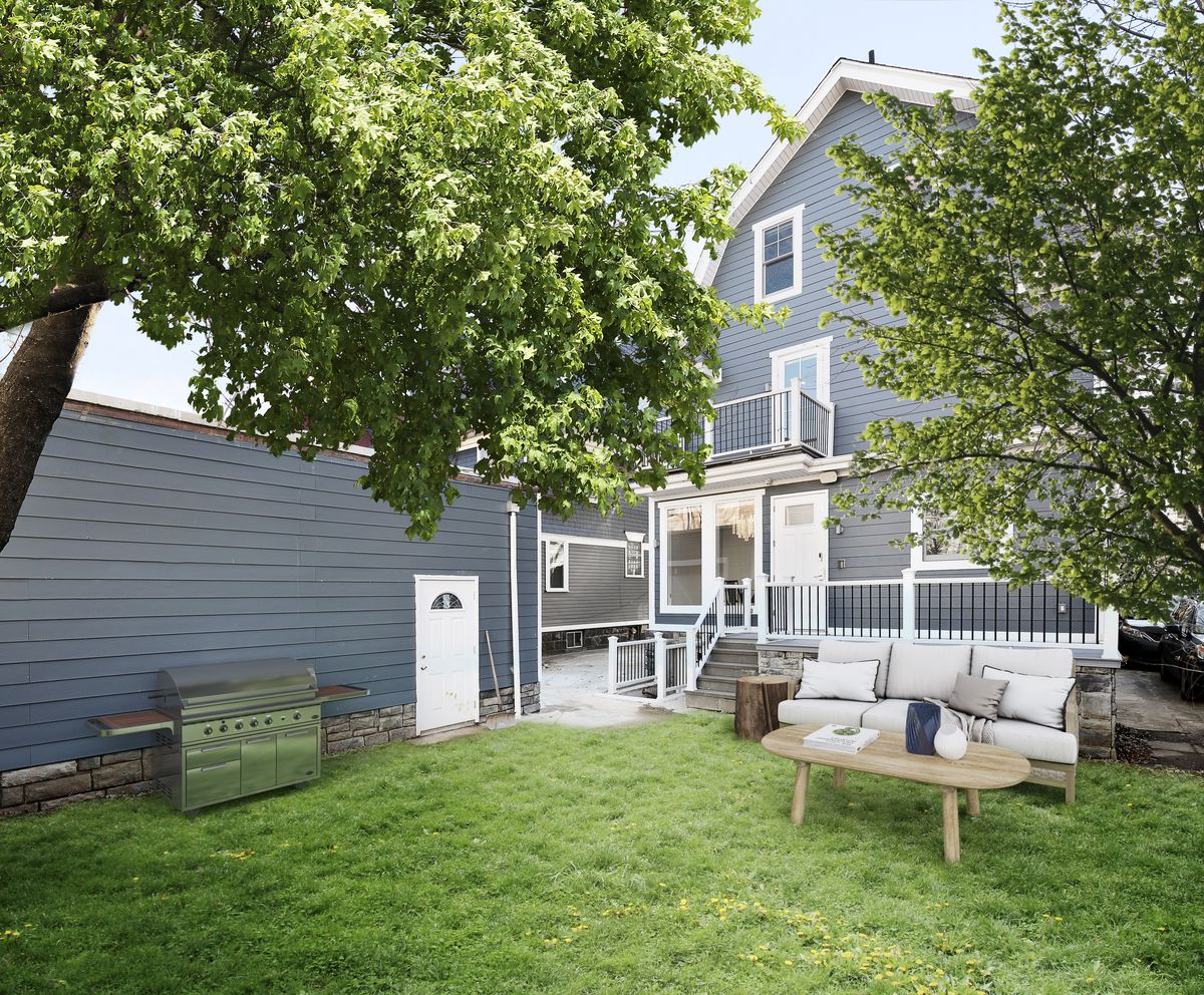 The exterior of a blue house, with a backyard that has some outdoor furniture and a large grill.