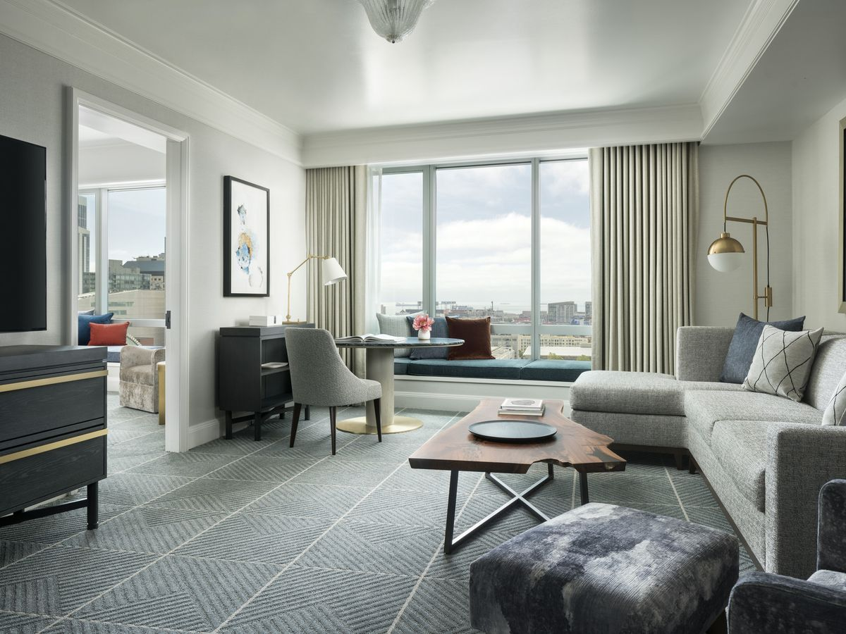 A room at the Four Seasons Hotel San Francisco. There is a couch, tables, chairs, windows, and works of art on the walls.