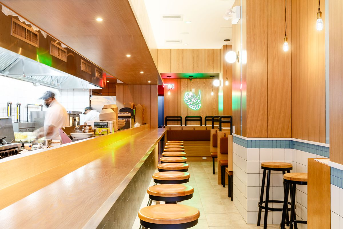 Blonde wood stools and a long wooden counter line the length of the indoor dining room and open kitchen; a green decorative neon sculpture hangs in back