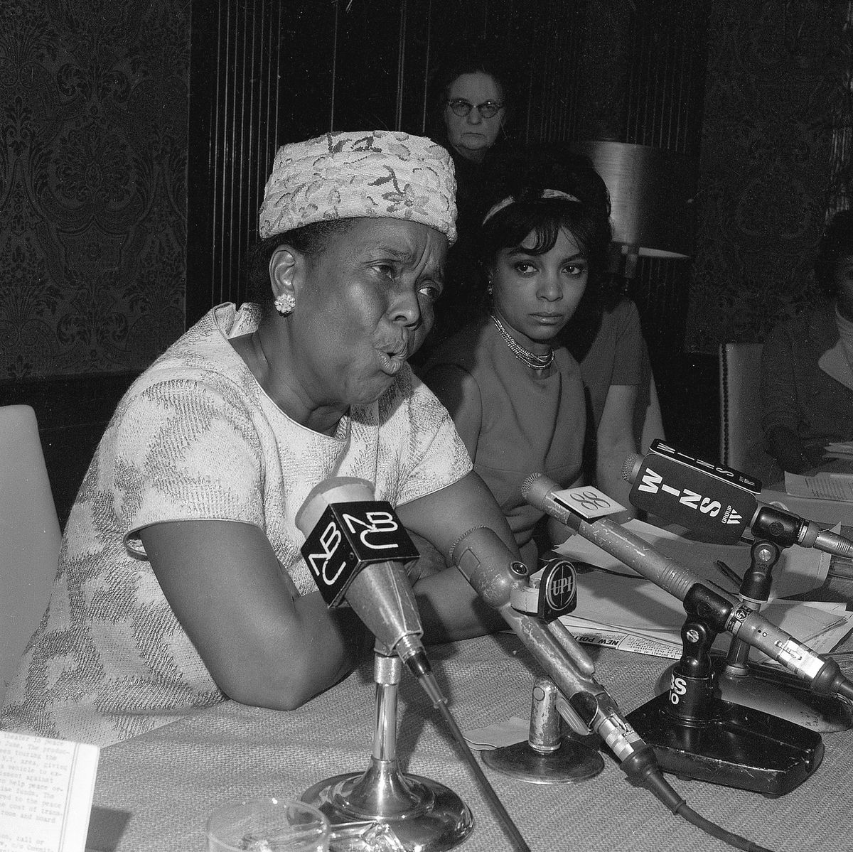 Baker, in a dress with a diamond print and a pill box hat covered in flowers, speaks emphatically into a group of microphones featuring the logos of news organizations like WINS, NBC, and EPI.