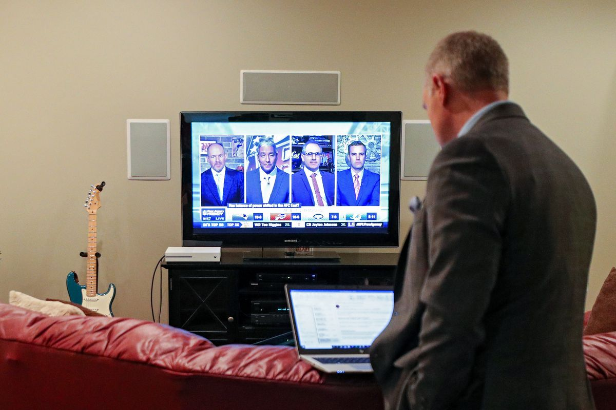 With the NFL Network on the television, WBALSports Anchor/Reporter Pete Gilbert checks his computer following a stand-up report on the 2020 NFL Free Agency and the Baltimore Ravens in the basement of WBAL Chief Sports Photographer Jim Forner's home basement on March 18, 2020 in Mount Airy, Maryland.