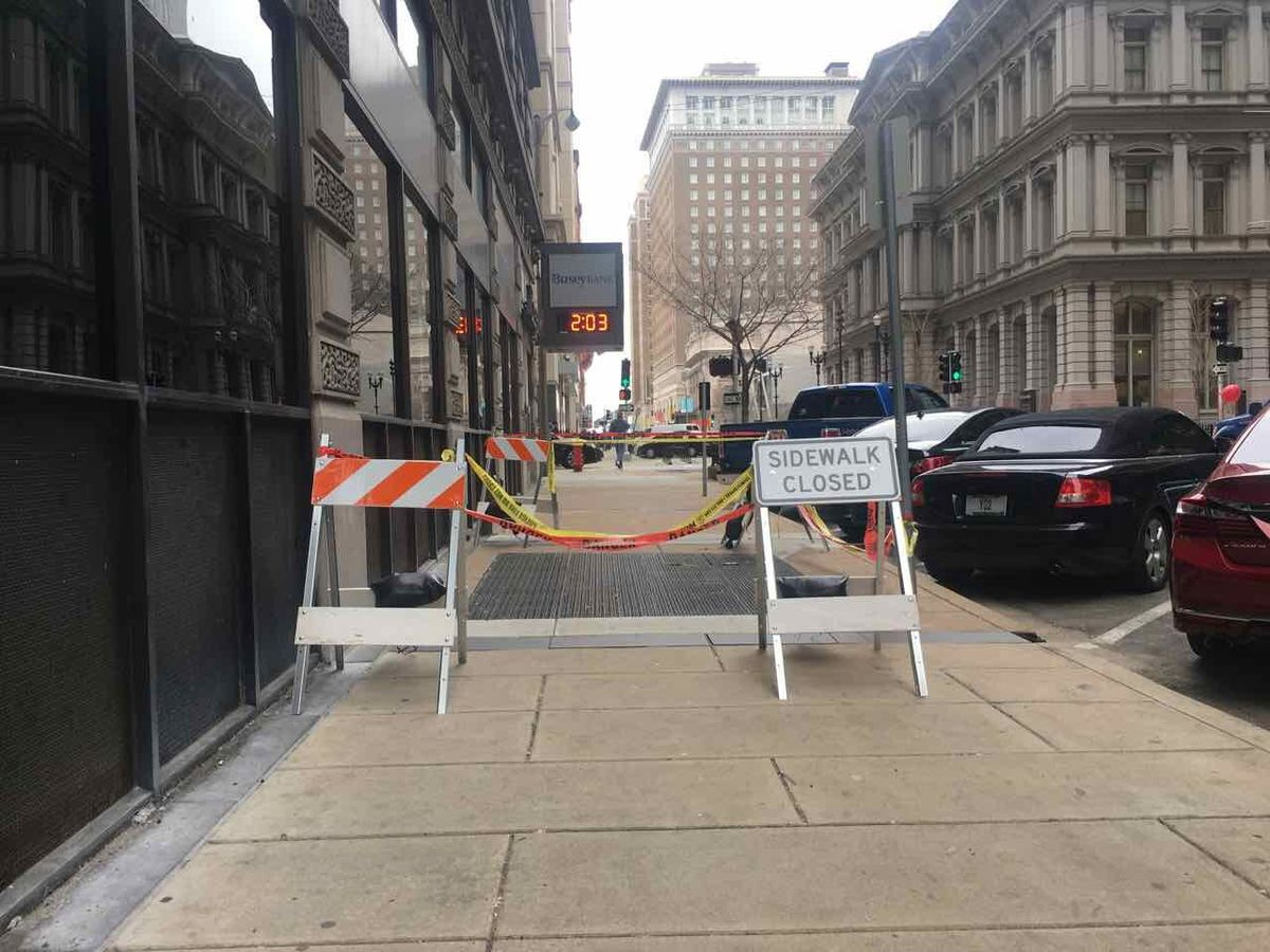 A wide sidewalk on a downtown street but nearly all of the sidewalk is closed with signs and caution tape.