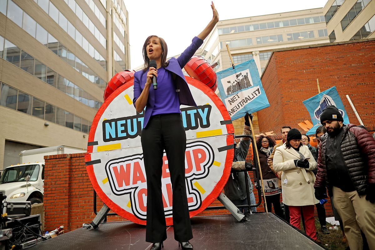 FCC commissioner Jessica Rosenworcel speaking into a microphone at a net neutrality rally.